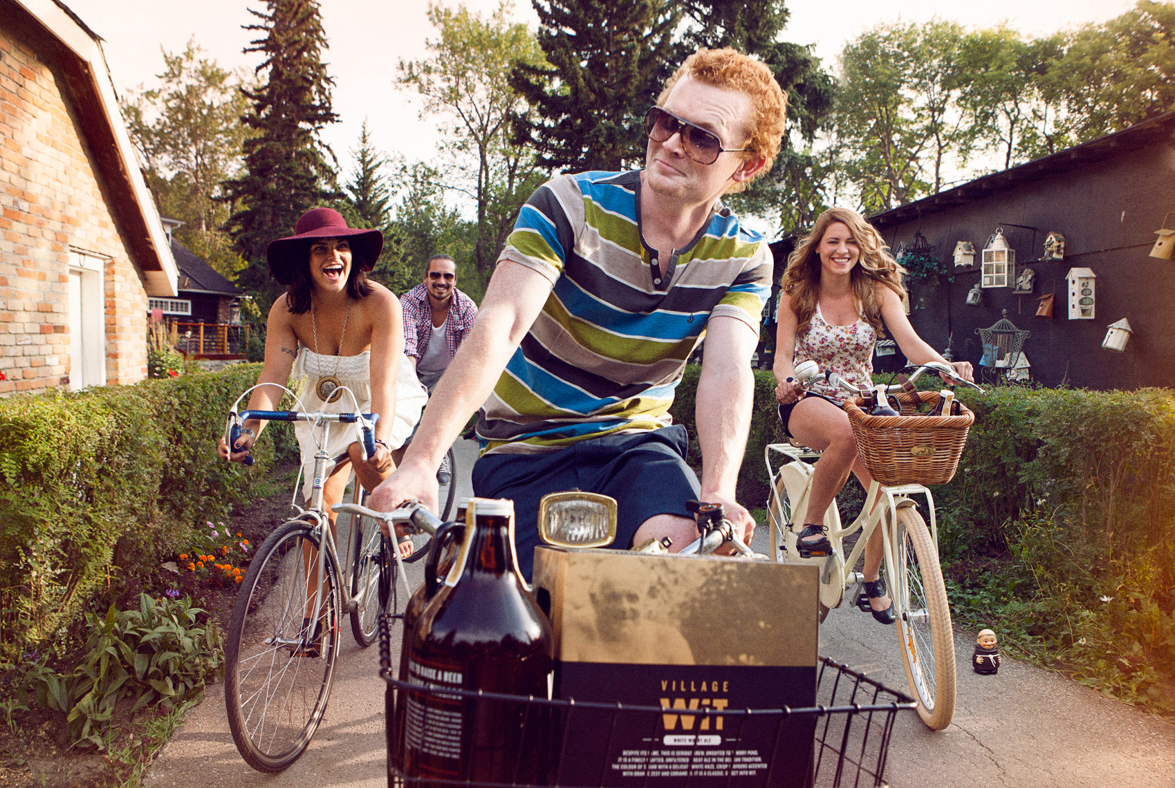 Red headed young man riding a bike with basket of beer and friends